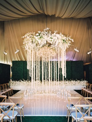 wedding-ceremony-white-flooring-flower-chandelier-with-garlands-of-orchids-and-crystals-at-altar