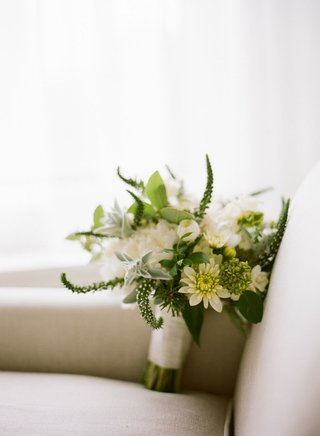 green-and-white-bridal-bouquet-wrapped-with-satin-white-ribbon-on-armchair