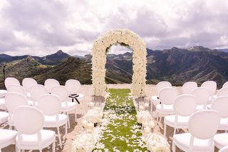 malibu-rocky-oaks-ceremony-white-chairs-ivory-floral-arch