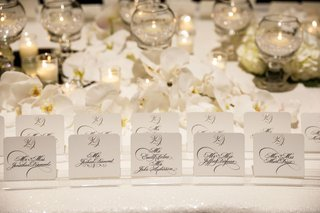 wedding-reception-escort-card-table-white-sequin-linen-white-orchid-tea-light-glass-orbs-calligraphy