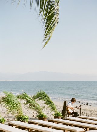 wedding-ceremony-on-beach-palm-fronds-leaves-plants-next-to-white-benches-on-sand-friend-playing