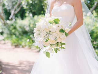 bride-in-strapless-a-line-monique-lhuillier-wedding-dress-holding-bouquet-with-white-flowers-vines