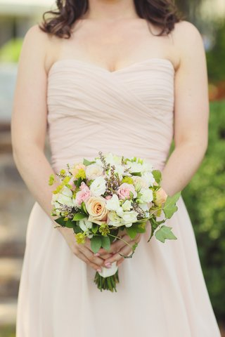 woman-in-champagne-dress-holding-freshly-picked-flowers