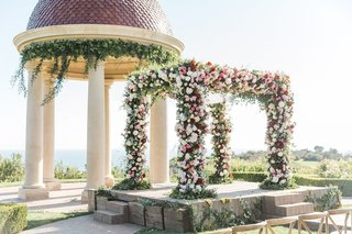 floral-vibrant-chuppah-front-of-dome-pelican-hill-resort-newport-wedding-red-pink-arch-california