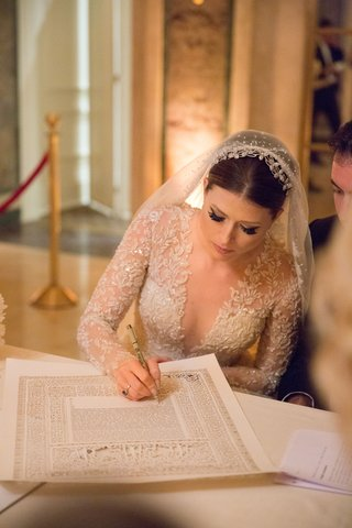 bride-in-reem-acra-wedding-dress-with-veil-and-long-sleeves-signing-ketubah-jewish-wedding