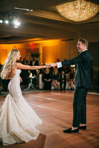 groom-smiles-as-he-dances-with-his-bride-in-berta-wedding-dress-bustle-for-dancing-chandelier