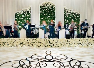 live-band-performing-on-wedding-stage-decorated-with-greenery-wall-white-rose-flowers-dance-floor