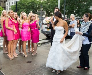 bride-walking-in-nyc-street-waves-to-bridesmaids
