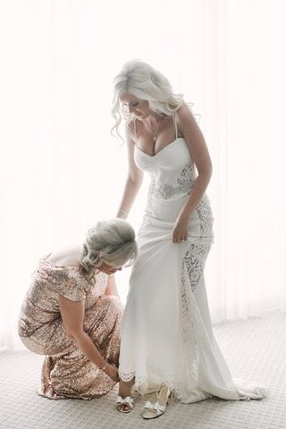 mother-of-the-bride-in-a-gold-sequined-badgley-mischka-dress-helps-her-put-on-white-kate-spade-shoes