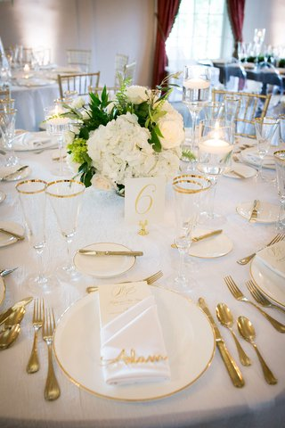 wedding-reception-table-white-linen-gold-white-charger-gold-flatware-white-low-centerpiece-glasses
