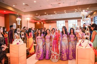 indian-bride-and-bridesmaids-in-saris-walk-down-the-aisle