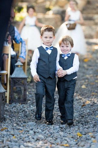 ring-bearers-in-grey-vets-and-blue-bow-ties-hold-hands-while-walking-down-the-aisle