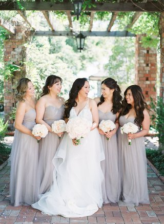 bride-in-v-neck-hayley-paige-wedding-dress-with-bridesmaids-in-strapless-light-grey-taupe-gowns
