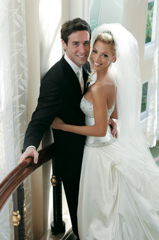 bride-in-a-veil-and-gown-with-a-beaded-bodice-and-pickup-skirt-and-groom-in-a-black-tuxedo
