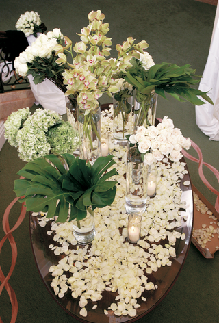 table-covered-with-white-rose-petals-and-decorated-with-roses-hydrangeas-orchids-and-fronds