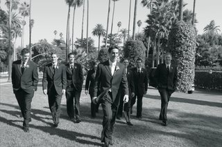 black-and-white-photo-of-groom-and-groomsmen-walking-on-the-lawn-of-the-beverly-hills-hotel