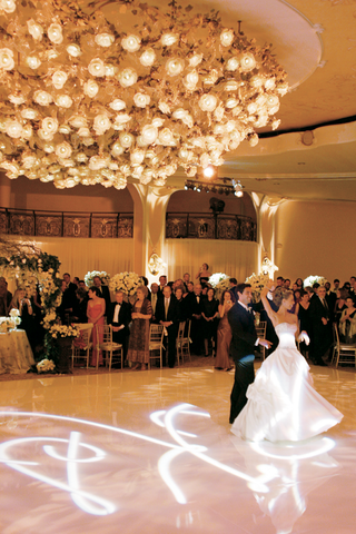 bride-and-groom-have-their-first-dance-on-a-custom-made-floor-beneath-a-floral-chandelier