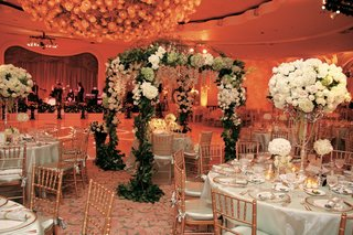 wedding-sweetheart-table-is-placed-under-a-canopy-of-greenery-green-and-white-flowers