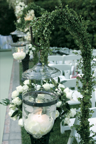 glass-vessel-filled-with-white-rose-petals-and-candle-hangs-from-a-hook-covered-in-greenery