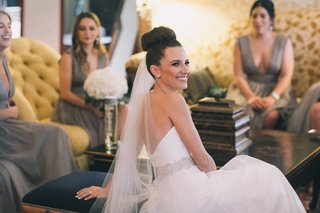 bride-in-romona-keveza-beaded-belt-sock-bun-lounging-with-bridesmaids