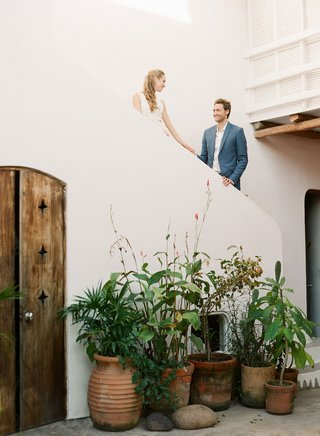 wedding-rehearsal-dinner-welcome-party-in-sayulita-mexico-couple-on-stairs-above-plants-in-pots