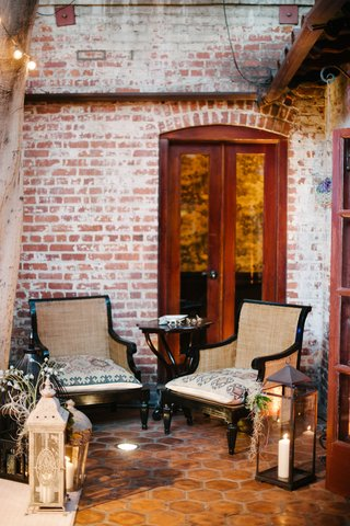 armchairs-on-tile-floor-with-brick-walls-and-lantern-decorations