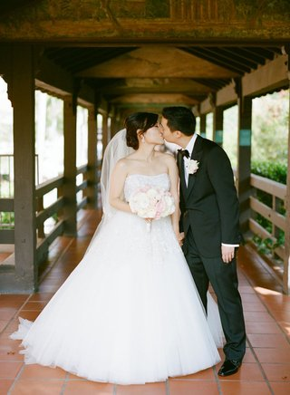 bride-and-groom-kiss-on-tiled-path-covered-with-wooden-roof