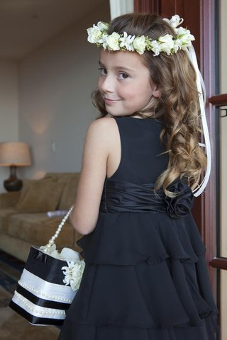 flower-girl-in-a-black-sleeveless-dress-with-a-tiered-skirt-and-white-floral-halo