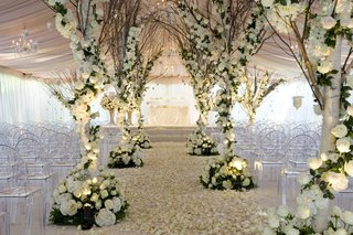 tented-wedding-ceremony-with-trees-wrapped-with-white-roses-and-hydrangeas