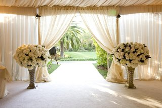 tented-wedding-ceremony-with-large-arrangement-of-white-flowers-at-the-entrance