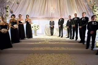 bridesmaids-in-strapless-black-gowns-and-light-bouquets-with-groomsmen-in-tuxedos-at-tented-ceremony