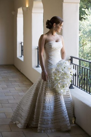 bride-in-a-strapless-vera-wang-gown-with-champagne-bands-holds-bouquet-of-orchids