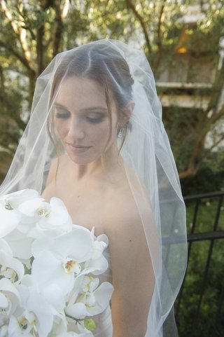 bride-in-a-veil-holds-white-orchid-bouquet
