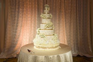 white-wedding-cake-with-gold-bands-and-swirls-and-white-roses