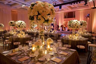wedding-reception-in-a-ballroom-draped-with-pink-fabric-and-light-arrangements-on-tables