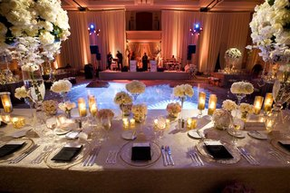 wedding-reception-table-decorated-with-tall-and-low-white-flower-arrangements