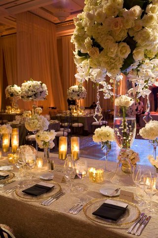wedding-reception-table-with-tall-and-small-white-flower-arrangements-and-candles