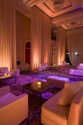 wedding-reception-lounge-area-with-plush-seating-draped-with-sheer-pink-fabric