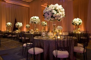 wedding-reception-with-chameleon-chairs-and-tables-with-tall-arrangements-of-light-flowers
