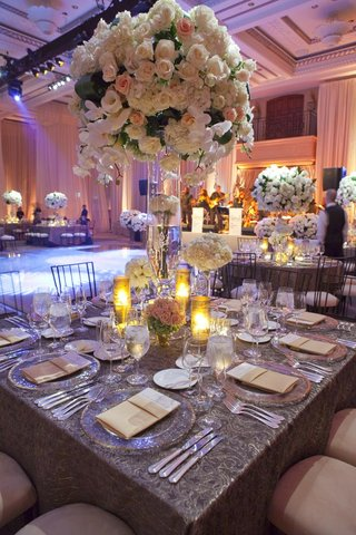 wedding-reception-table-with-a-tall-centerpiece-of-light-flowers-surrounded-by-low-arrangements