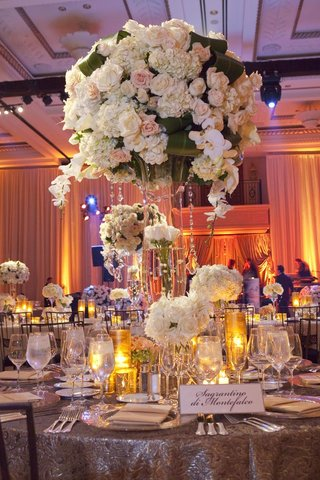 wedding-reception-table-with-light-tall-and-low-floral-arrangements-and-candles