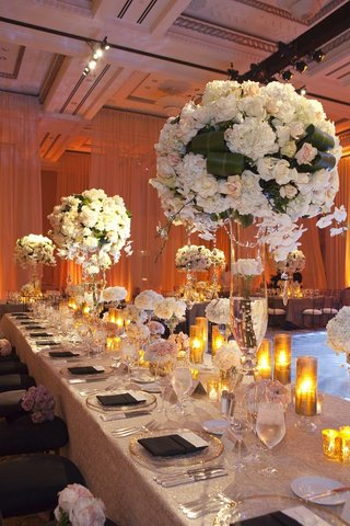 wedding-reception-table-with-tall-light-floral-arrangements-and-candles-in-golden-hurricanes