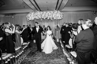 black-and-white-photo-of-bride-and-groom-husband-wife-recessional-walking-up-carpet-aisle-candles