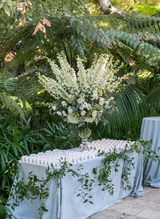 wedding-reception-escort-card-table-white-flowers-in-glass-vase-on-table-with-tent-escort-cards