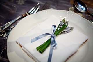 wedding-reception-place-setting-is-decorated-with-a-small-bundle-of-flowers