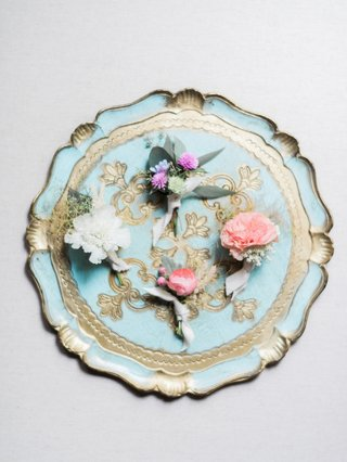 bohemian-inspired-boutonnieres-placed-on-ornate-plate