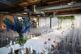 wedding ceremony industrial venue open duct and beams white aisle runner ghost chairs candles blue