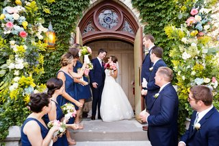 bride-and-groom-at-top-of-stairs-outside-church-with-bridesmaids-and-groomsmen-in-navy-blue
