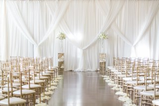 aisle-with-flower-petals-and-white-backdrop-at-biltmore-ballrooms-in-atlanta-gold-chairs