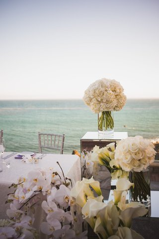 white-calla-lilies-and-orchids-around-the-bride-and-grooms-seat-at-the-reception